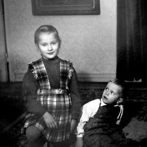 Taiteilija Riitta Nelimarkka ja pikkuveljensä Esa lapsuudenkodissaan Helsingin Töölönkadulla. Mustavalkoinen kuva, jossa Riitalla on villainen ruutumekko päällään ja pkkuveli katsoo häntä hämmästyneenä.