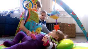 Lapsia olohuoneen lattialla.