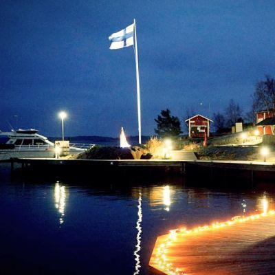 En stor motorbåt förtjöjd vid en upplyst brygga på Örö.