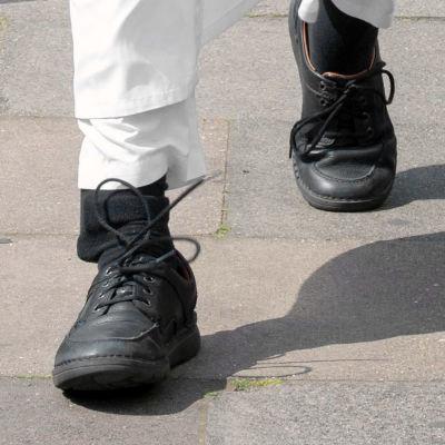 Fötter med svarta skor och svarta strumpor. Under syns en fotboja.