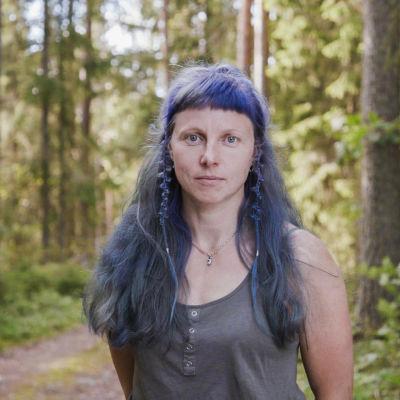 Käsityötaiteilija Elena Bondar lähikuvassa. Taustalla näkyy metsää.