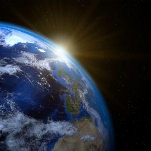 Maapallo, jonka takaa paistaa aurinko.