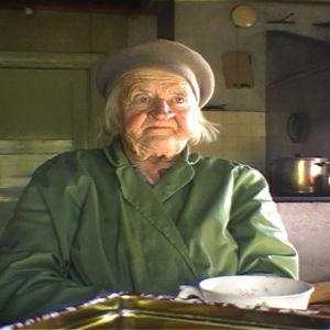 Vanha nainen istuu tuvassa pöydän ääressä.