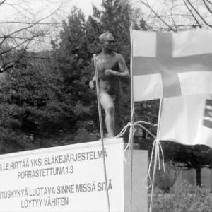 Protestimarssija Arvo Saarisen vaatimuslista Paavo Nurmen patsaan edessä.