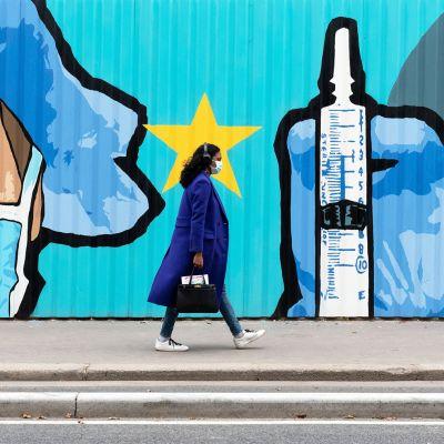 Henkilö kävelee seinämaalauksen edessä.