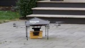 En liten drönare med Amazon.coms logotyp är på marken och har en liten orange låda nertill.