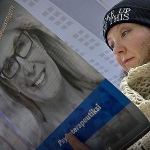 En kvinna läser en broschyr om psykoterapi.