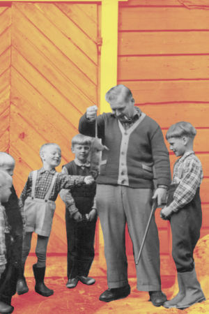En man håller upp en råtta framför pojkar.