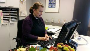 Mia Bäck sitter vid sitt arbetsbord och skriver på datorn.