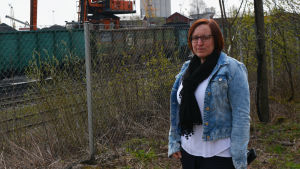 En kvinna står vid ett staket. Bakom staketet synns tågvagnar, stora kolhögar och en arbetsmaskin.