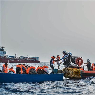 Hjälparbetare hjälper migranter ombord en orange gummibåt, fartyget Ocean Viking i bakgrunden.