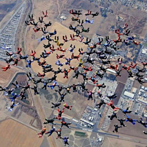 130 fallskärmshoppare faller i en snöflingeformation högt över marken.