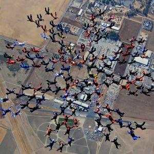 människor hoppar fallskärm i formation.