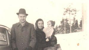 Laura Kolbe med föräldrar 1959 på vinter vid bil. Laura i mammas famn.