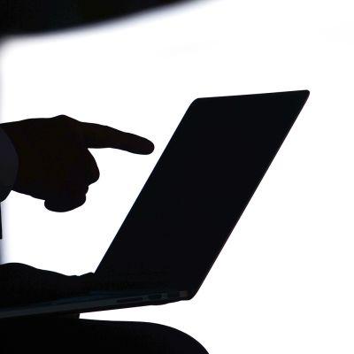 Sormi osoittaa kannettavan tietokoneen ruutua.
