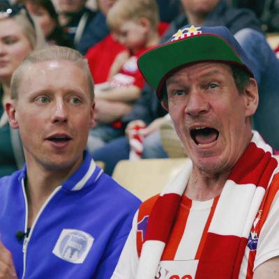 Kaksi miestä istuu katsomossa, toinen huutaa ja toinen taputtaa. Taustalla muita katsojia.