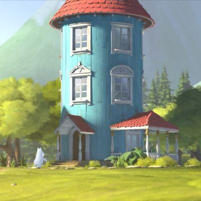 Valkoinen, pyöreä Muumipeikko menossa sisälle siniseen ja korkeaan Muumitaloon aurinkoisena kesäpäivänä.