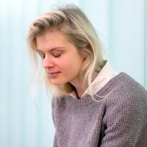Alina Tomnikov istuu kuvassa silmät kiinni, taustalla valoa ja lasiseinä.