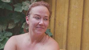 Nainen istuu ulkona saunan edustalla kesällä tukka märkänä.