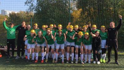Ett fotbollslag står i två rader. Tjejerna har guldhattar på huvudet och ser glada ut.