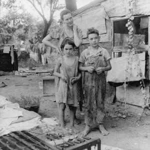 Köyhä perhe resuisissa vaatteissa majansa edessä
