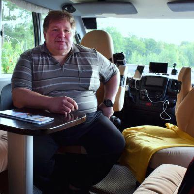 Mikael Lindström sitter i förarsätet på sin stora husbil.