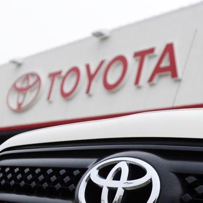 Toyotan liikemerkki auton keulassa ja talon seinässä.