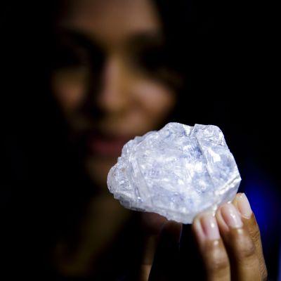 Nainen pitelee suurikokoista timanttia.