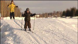 Barn åker skidor på vintern
