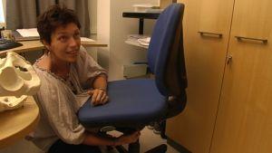 Arbetsfysioterapeut Cathlene Andersson justerar stolen