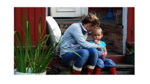 Nainen ja lapsi mökin portailla