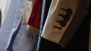 fyra knappar på kostymjackans ärm