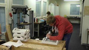 Walter Vikström (i rött) och Fredrik Ahlgren (i grönt) gör träprodukter av egen design