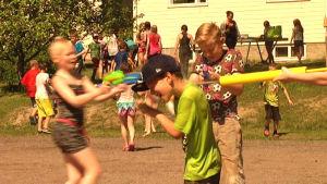 Vattenkrig pågår. Pojke får vatten i nacken.