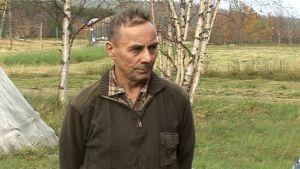 mies seisoo, taustalla heinäpeltoa ja osa laavusta