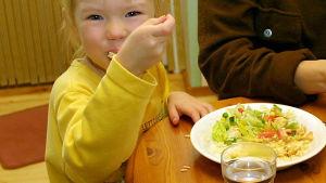 Litet barn stoppar mat i munnen.
