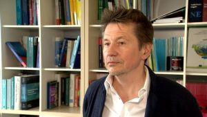 Professor Alex Housen fotograferad i sitt arbetsrum i Bryssel. I bakgrunden syns en bokylla med facklitteratur.