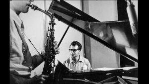 Saksofonista edessä ja pianisti takana mustavalkoisessa kuvassa.