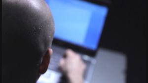 En person som sitter vid en laptop, bakgrunden är suddig.