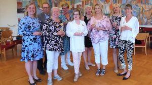 Åtta kvinnor och en man står uppradade för gruppfotografering. De har höga champagneglas i sina händer och är festklädda.