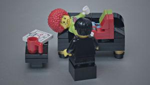 En legogubbe i terapisoffan tillsammans med en psykolog (hen också legogubbe).