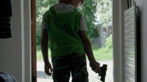Barnet Iivari Raittinen med en pistol i handen.