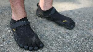 två mans ben med fivefingers skor.