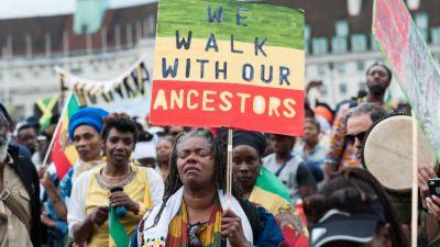 """En kvinna går längst fram i en marsch med en skylt där det på engelska står """"We walk with our ancestors"""""""