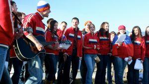 Venäläisryhmä laulaa urheilutakeissaan
