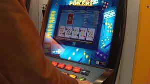 Anonym person spelar poker på en penningautomat