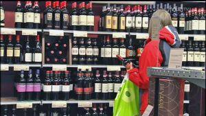 Anonym kvinna tittar på vinflaskor i Alko