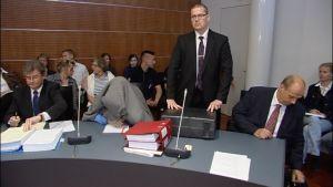 Den åtalade gömde sig under sin kavaj i rättssalen. Bredvid står sjukhusets juridiska ombud Peter Fjällström.