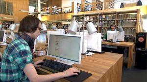 Mies ja nainen kirjaston tietokoneilla