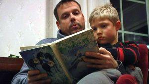 Pappa Johan Lindberg och pojken Adrian Lindberg sitter tillsammans och läser